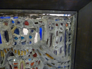 Interior of the panel, areas where the glass has fallen away from the plaster are illuminated by the light shining through from behind